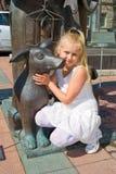 Mädchen, das in einer Umarmung mit einem Bronzehund sitzt Lizenzfreies Stockfoto