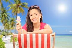 Mädchen, das Eiscreme auf einem tropischen Strand isst Lizenzfreie Stockfotografie
