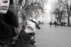 Mädchen, das elektronische Zigarette, Iqos, schwarz u. weiß raucht stockfotos