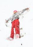 Mädchen, das Engel im Schnee macht Stockfoto