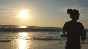 Mädchen, das entlang Ozeanufer während des Sonnenaufgangs rüttelt Schattenbild der jungen Frau laufend auf Seestrand bei Sonnenun