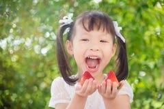 Mädchen, das Erdbeeren und Lächeln zwischen Picknick hält lizenzfreies stockbild