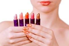 Mädchen, das fünf Lippenstifte anhält Lizenzfreie Stockbilder