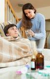 Mädchen, das für kranken Ehemann im Wohnzimmer sich interessiert Lizenzfreies Stockbild