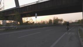 Mädchen, das Fahrrad aus dem Sattel in Richtung zur Brücke heraus auf Sonnenuntergang fährt Langsame Bewegung
