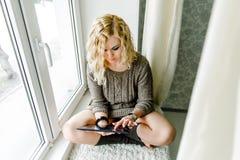 Mädchen, das am Fenster mit der Tablette sitzt Stockfotografie