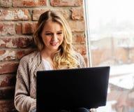 Mädchen, das am Fenster mit Laptop sitzt Stockfoto