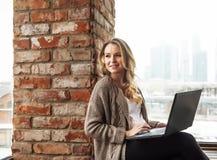 Mädchen, das am Fenster mit Laptop sitzt Lizenzfreie Stockfotos