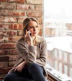 Mädchen, das am Fenster mit Laptop sitzt Lizenzfreies Stockfoto