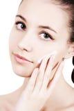 Mädchen, das Feuchtigkeitscremesahne auf Gesicht aufträgt. Lizenzfreie Stockfotos