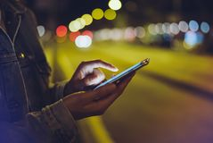 Mädchen, das Finger auf Schirm Smartphone auf Hintergrundbeleuchtungsglühen bokeh Licht in der Nachtatmosphärischen Stadt, Hippie stockfotos