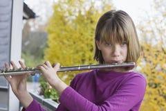 Mädchen, das Flöte spielt Stockfotos