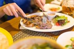 Mädchen, das Fleisch mit Salat in einem Restaurant isst stockbild