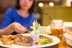 Mädchen, das Fleisch mit Salat in einem Restaurant isst stockfoto