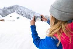 Mädchen, das Foto auf intelligentem Telefon Snowy-Gebirgsjunge Frauen-Winter-Schnee macht Lizenzfreies Stockfoto