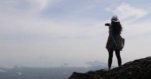 Mädchen, das Foto der Landschaft von der Gebirgsspitze am Zellintelligenten Telefon, weiblicher Tourist mit dem Rucksack steht au stock video