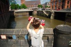 Mädchen, das Foto von der Stadt unter Verwendung des intelligenten Telefons macht Stockbilder