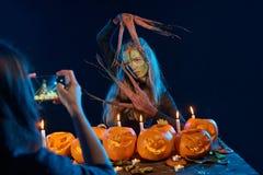 Mädchen, das Foto von Halloween-Frau mit ihrem intelligenten Telefon gefangennimmt Stockfoto