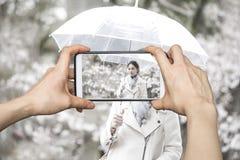 Mädchen, das Fotos am intelligenten Mobiltelefon am japanischen Frauenesprit macht Stockfotografie