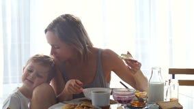 Mädchen, das frühstückt und seinen Sohn küsst stock video footage