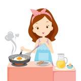 Mädchen, das Fried Egg For Breakfast kocht Stockbilder