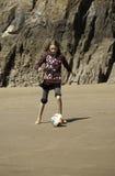 Mädchen, das Fußball auf dem Strand spielt Stockfotos