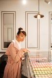 Mädchen, das Gebäck durch Glasschaukasten auf das Café betrachtet Lizenzfreies Stockfoto