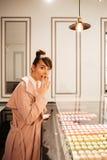 Mädchen, das Gebäck durch Glasschaukasten auf das Café betrachtet Stockbilder