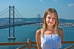 Mädchen, das gegen die Brücke in Lissabon aufwirft Stockfotografie