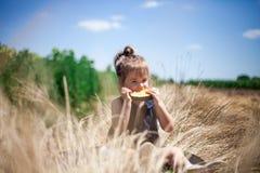 Mädchen, das gelbe Wassermelone in einer Wiese isst stockfotos