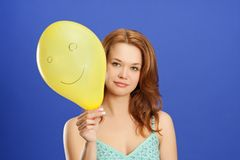 Mädchen, das gelben lächelnden Ballon anhält Stockfotos