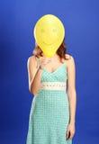 Mädchen, das gelben lächelnden Ballon anhält lizenzfreie stockfotos