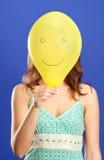 Mädchen, das gelbes lächelndes nahes hohes des Ballons anhält Stockbild
