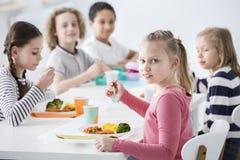 Mädchen, das Gemüse mit Freunden in der Kantine während des Bruches isst lizenzfreies stockfoto