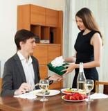 Mädchen, das Geschenk während des romantischen Abendessens gibt stockbild