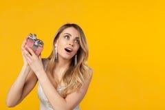 Mädchen, das Geschenkbox rüttelt Lizenzfreie Stockfotografie