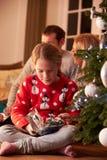 Mädchen, das Geschenke durch Weihnachtsbaum auspackt Lizenzfreies Stockfoto
