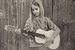 Mädchen, das Gitarre durch Scheune im Nebel spielt Stockfotografie