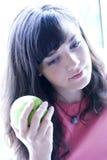 Mädchen, das grünen Apfel anhält Stockfotos