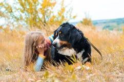 Mädchen, das großen Hund auf Herbstweg ausbildet stockbild