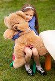 Mädchen, das großen Teddybären beim Sitzen auf Stuhl am Yard umarmt Lizenzfreie Stockfotos