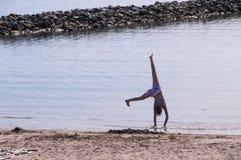 Mädchen, das Gymnastik auf dem Strand tut Lizenzfreie Stockfotografie