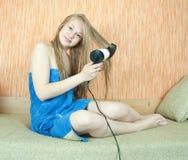 Mädchen, das hairdrye und Kamm verwendet Stockfoto