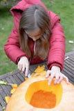Mädchen, das Halloween-Kürbis macht stockfotos