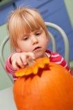 Mädchen, das Halloween-Kürbis macht Stockbild