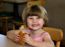 Mädchen, das Hamburger isst Stockbilder