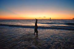 Mädchen, das Handstand über blauem Meer auf buntem Sonnenuntergang an Clearwater-Strand tut stockbild