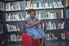 Mädchen, das Handy beim Sitzen gegen Bücherregal in der Bibliothek verwendet stockfotografie