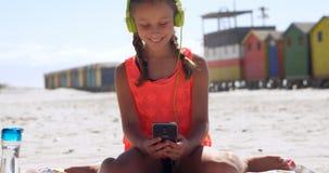 Mädchen, das Handy im Strand 4k verwendet stock footage