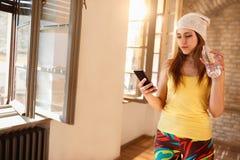 Mädchen, das am Handy Innen schaut Lizenzfreies Stockfoto